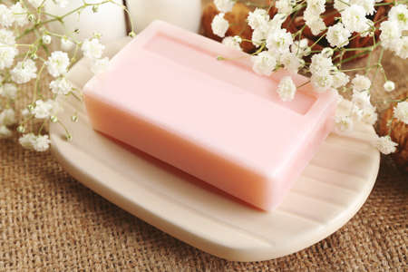 Soap on a dish over wooden background, close up