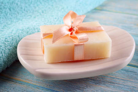 Soap with ribbon on a dish over wooden background, close up Stock Photo