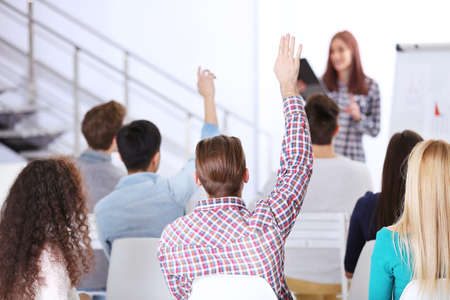 Young man with raised hand sitting back at the office meeting Stock Photo