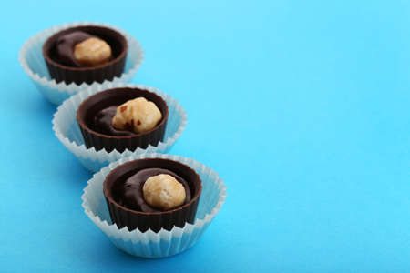 Three chocolate candies with nuts in paper cups, on blue background Stock Photo