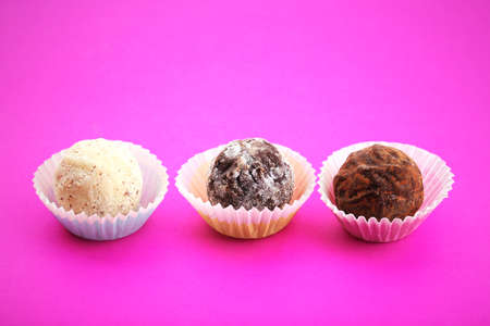 Three chocolate truffles in paper cups, on pink background