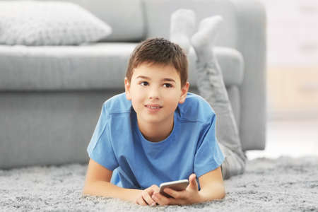 Boy lying with mobile phone on a carpet at home Stock Photo