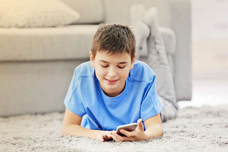 Boy using his mobile phone at home
