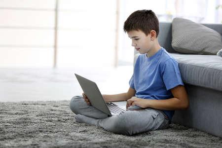 Weinig jongen die laptop op een vloer thuis met behulp van
