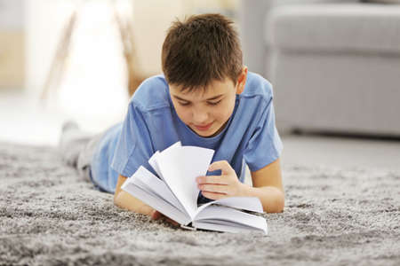 Boy reading book on a floor at home