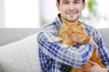 Young man with fluffy cat sitting on a sofa