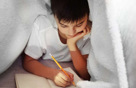 Little boy writing with pencil under the blanket