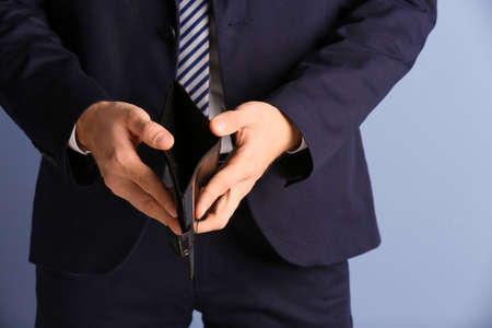 Man in a suit showing an empty purse on blue background Banco de Imagens