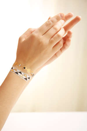 Silver and golden flash tattoo on female wrist over white background