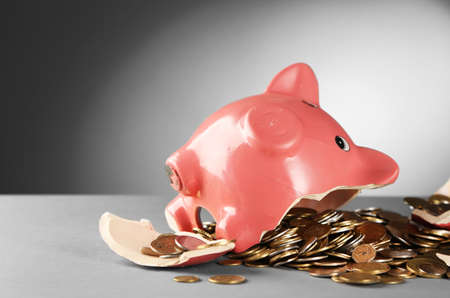 Broken piggy bank on the table against grey background, close up