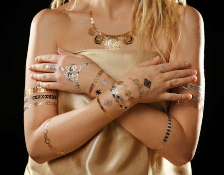Young blonde girl with golden and silver flash tattoo on black background Stock Photo