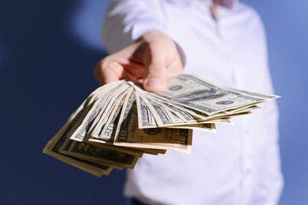 Hombre sujetando el abanico de billetes de dólar sobre fondo azul. Foto de archivo