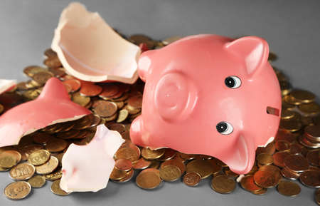 Broken piggy bank with pile of coins on grey background, close up Stock Photo
