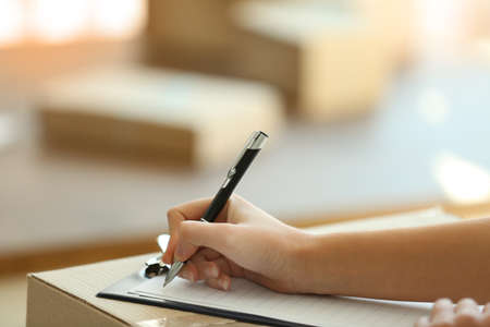 Delivery concept. Woman signs papers among parcels, close up Stock Photo