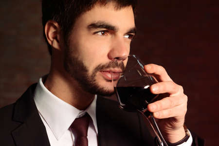 Man sniffing red wine in glass on brick wall background Imagens - 97525203