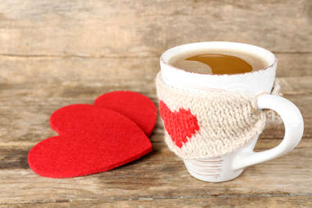 Cup of coffee with red felt hearts on wooden background, close up