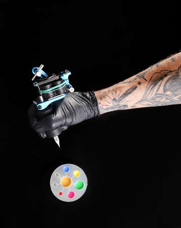Tattooist hand in medical glove with tattoo machine and colourful inks on black background Stock Photo