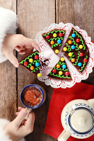 Christmas concept. Santa have a meal. Tasty chocolate cake and cup of coffee on wooden background, close up