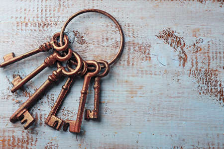 Bunch of old keys on blue wooden background, close up