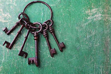 Bunch of old keys on green scratched wooden background, close up