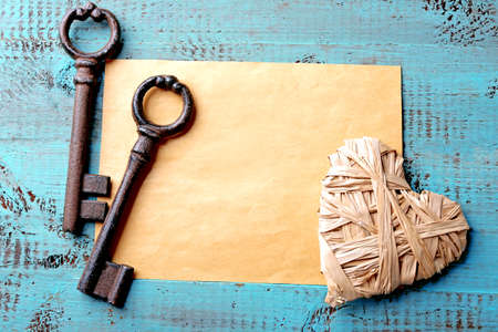 Old key with decorative heart and sheet of paper on blue wooden background, close up Stockfoto