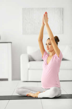 Health concept. Young beautiful pregnant woman does yoga exercise in the modern room Stockfoto