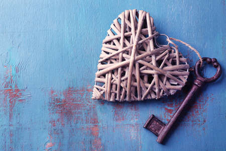 Old key with decorative heart on blue wooden background, close up