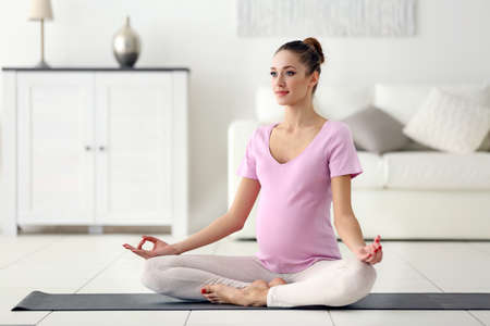 Health concept. Young beautiful pregnant woman does yoga exercise in the modern room Stock Photo