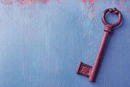 Old key on blue wooden background, copy space