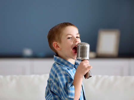 Little boy singing into the microphone at home