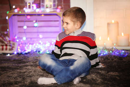 Little boy sitting at home on a Christmas background