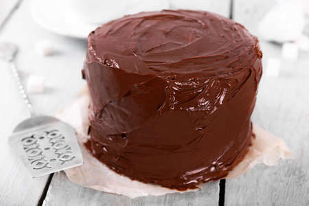 Chocolate cake with blade on a wooden table background Stock Photo