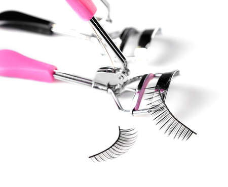 Two curlers and false eyelashes, isolated on white Stock Photo