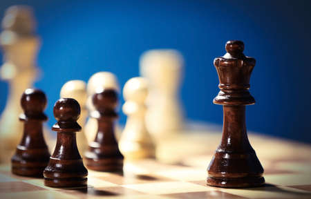 Chess pieces and game board on blue blurred background Stock Photo