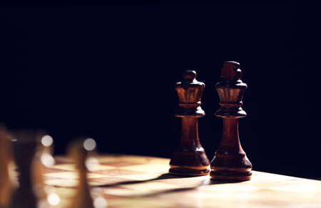 Chess pieces and game board on black background Stock Photo