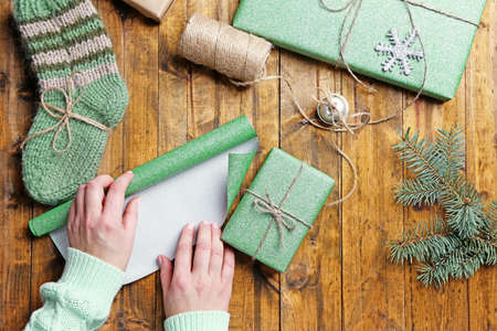 Female hands preparing gifts for Christmas on wooden table