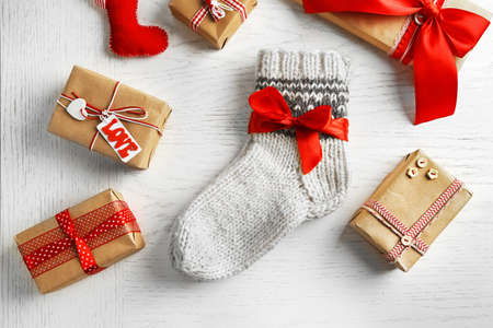Pair of knitted socks with wrapped gifts on light table