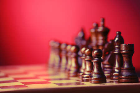 Chess pieces and game board on red blurred background Stock Photo