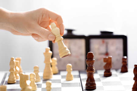Female hand playing chess on light blurred background Stock Photo