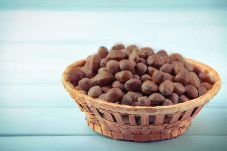 Hazelnuts in wicker basket on color wooden background