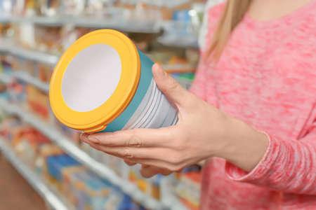 Giovane donna che sceglie alimenti per bambini in supermercato, primo piano