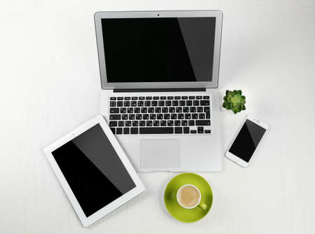 Different modern devices with green plant and cup of coffee on light table
