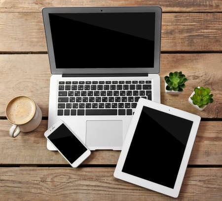 Different modern devices with green plants and cup of coffee on wooden table