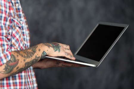 Young man with tattoo holding laptop on grey background Stock Photo