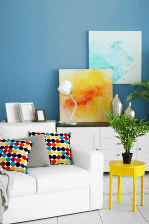 Living room interior with white furniture, green plants and pictures on blue wall background