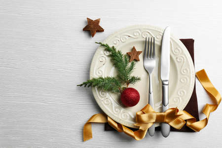 Christmas serving cutlery on plate over light wooden table Standard-Bild