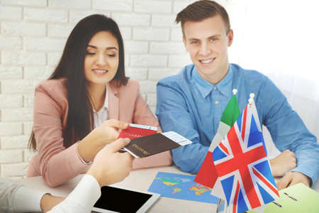 Agent giving passports and tickets to customers in the office of travel company Stock Photo