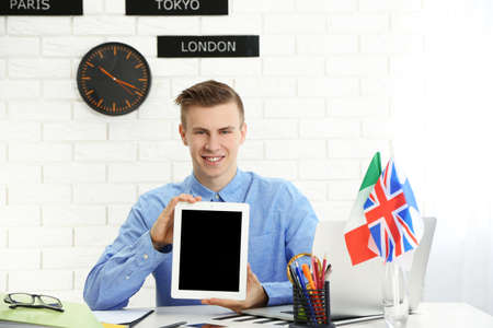 Young man showing tablet in the office of travel company Archivio Fotografico - 97525320