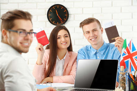 Agent and happy young couple with passports and tickets in the office of travel company Stock Photo