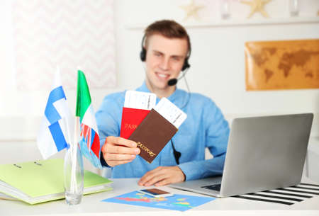 Young man talking on headset and showing passports with tickets in the office of travel company